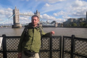 Ein junger Mann steht vor der Tower Bridge in London.